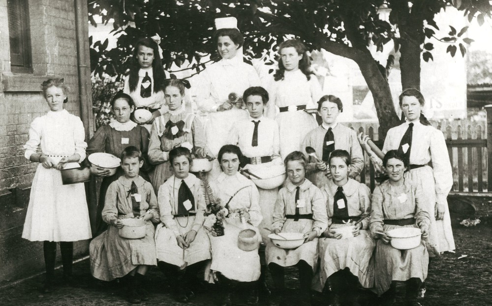 Cooking classes in public schools were established in 1897. This group shows girls holding basins, pots, spoons and what may be a rolling pin. The teacher is wearing apron and cap. Burwood Public School Cookery Class, 1908. Digital ID 15051_a047_002139