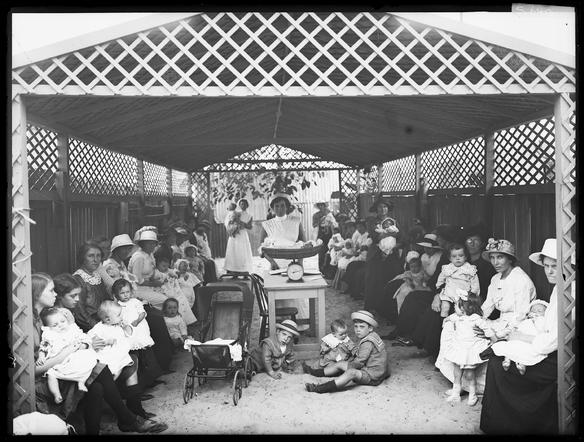 Mothers and infants wait in the back yard of the Alexandria baby clinic, the first of many opened by the NSW government during the War to improve infant health. Waiting to see Doctor, Baby Health Centre, Alexandria, 1914. NRS 4481 ST 5640