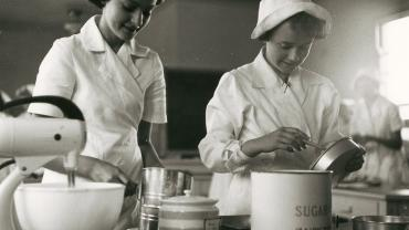 These two girls may be whipping up a cake or a sponge. During the 1950s girls taking part in cooking classes wore nurse-like white uniforms with caps. Bathurst High School, 1954. Digital ID 15051_a047_000772