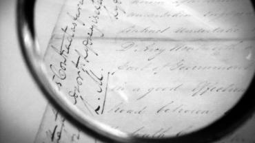 Black and white magnifying glass over paper record
