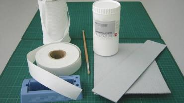 Fig. 3 - Materials clockwise from top left, cotton tape, Lascaux, corrugated board, gummed linen tape. Included are a roller damper for wetting the linen tape and a brush for applying the adhesive