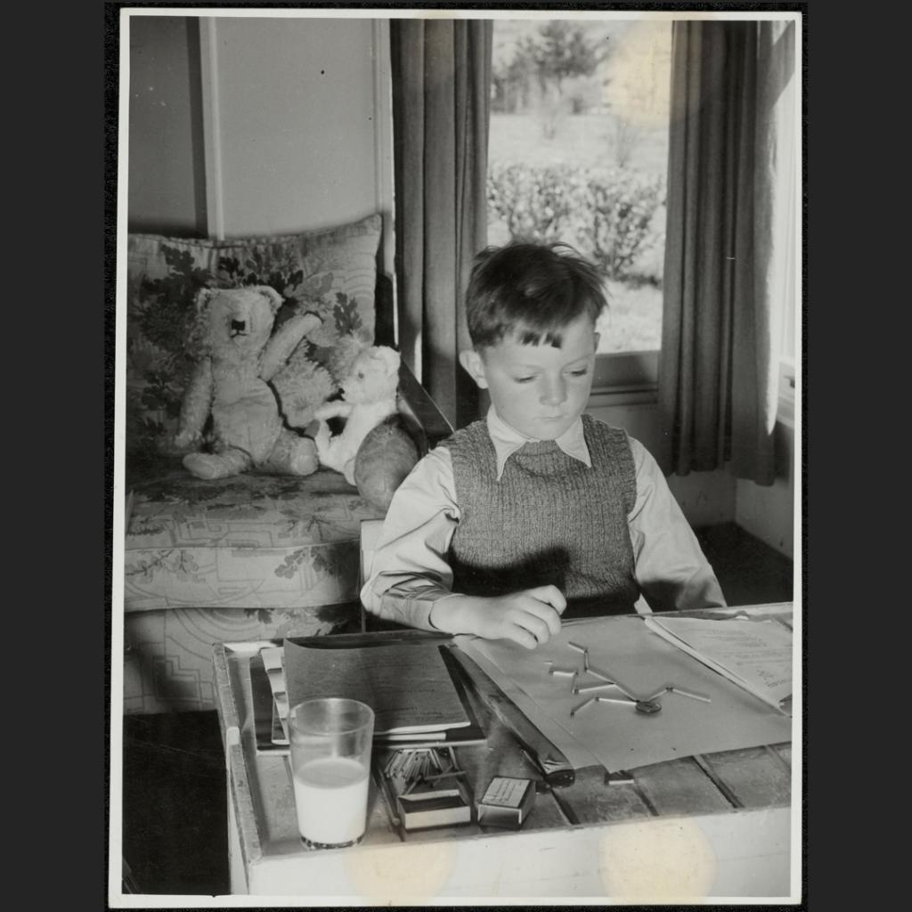 A boy fortified by a glass of milk and supported by his teddy bears and football successfully completes a button and match stick man as a exercise for his State Correspondence School teacher.